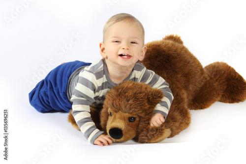 Poster Ein kleiner Junge kuschelt mit einem Plüschbären