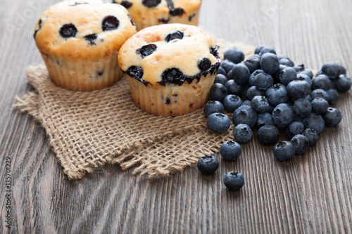 Poster muffin with blueberries on a wooden table. fresh berries and swe