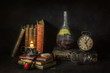 Classic still life with vintage books placed with old wine bottle,clock, glass of wine,pipe and vintage illuminated candle on rustic dark background..