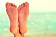 Perfect clean female feet with sea sand on the beach . Spa ,scrub and foot care . Foot massage .