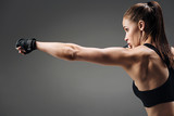 Active girl boxing on a grey background