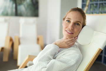 Beautiful woman relaxing in bathrobe in resort