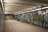 Abandoned underground walk-through with graffiti wall at night.