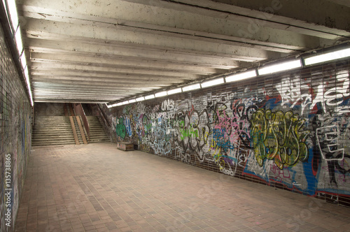 Foto op Plexiglas Graffiti Abandoned underground walk-through with graffiti wall at night.