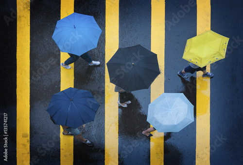 Rainy Day in Hong Kong. Crossing the street in the crosswalk with a colorful umbrella during a torrential rain and wind storm.