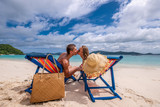 Couple kissing on tropical beach in loungers