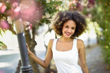 Young black woman with afro hairstyle smiling in urban park