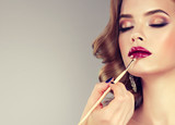 Hand of make-up master, painting lips of young beautiful model. Makeup in progress.  - 135798242