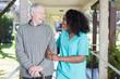 African nurse assisting elderly man outdoor