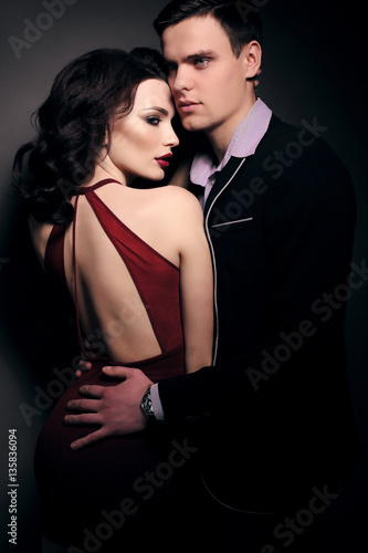 fashion studio photo of lovely impassioned couple in elegant out
