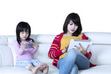 Little girl and mother holding gadgets