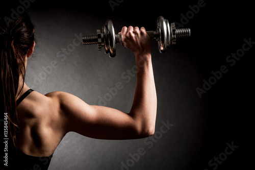 Atractive fit woman works out with dumbbells as a fitness concep Poster