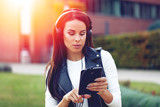 Young woman listening music on tablet by headphones in sunset