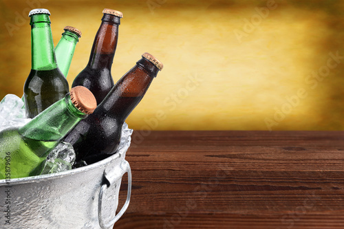 Closeup of a metal ice bucket filled with assorted beer bottles Poster
