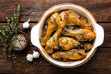 Roasted chicken legs on rustic wooden background, top view