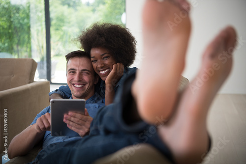 Poster multiethnic couple relaxing at  home with tablet computers