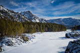 Magnificent views of the mountainous terrain in the winter with a frozen river