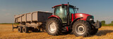 Modern agricultural tractor with trailer on the wheat field after harvest