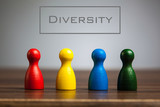 Diversity concept with four pawn figurines on table, grey backgr - 135924698