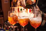 Fototapety tre cocktail Aperol al bar. Il barista versa champagne in un bicchiere