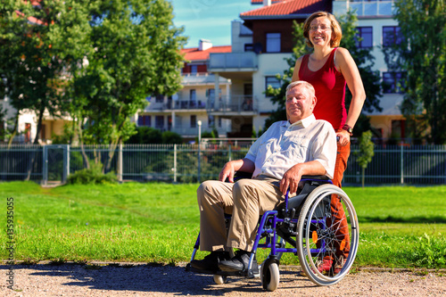 man on wheelchair with young woman Poster