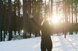 teen girl raised hands from behind in winter pine forest in sunset, freedom or victory concept