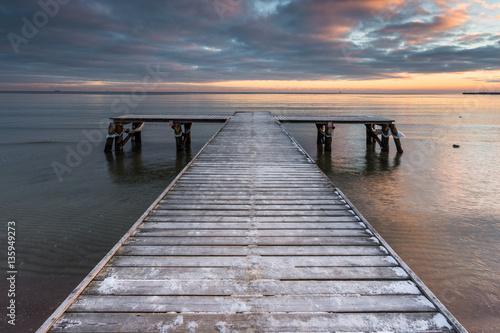 Wczesnym rankiem w zamarzniętym małym molo na plaży w Sopocie. Zimowy krajobraz w Sopocie, Polska.