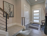 Bright entryway with creamy walls and hardwood floor - 135953277