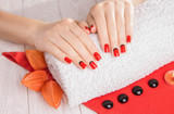 Red manicure with dekor and towel on white wooden table.