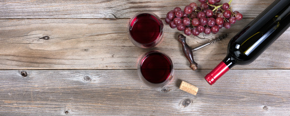 Unopen bottle of red wine and glasses with grapes on rustic wood © tab62