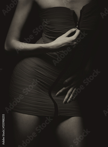 Poster Sexy woman  in tight skirt or dress undressing in sepia tones