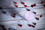 Glass of cherry smoothie on wooden table with cherries