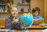 smiling girl showing on globe at school classroom. Educational and school concept
