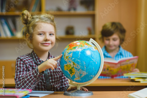 Plagát smiling girl showing on globe at school classroom
