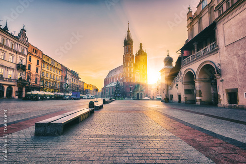 Krakow, main architectural ensemble, amazing colors of sunrise over the old town Market square, St. Mary's church (Mariacki cathedral) and Cloth Hall (Sukiennice), Poland, Europe