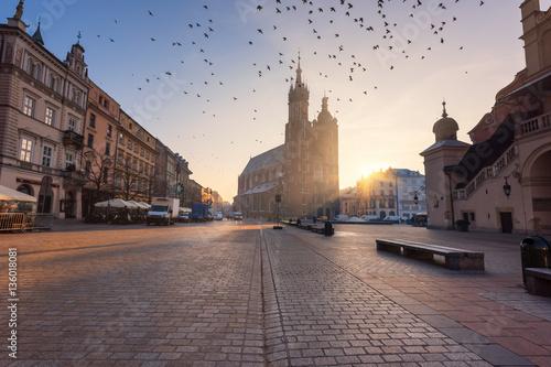 Rynek w Krakowie, latające gołębie nad kościołem Mariackim (katedra Mariacka) o wschodzie słońca, poranny pejzaż miejski, Polska, Europa