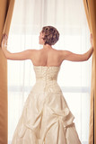 elegant bride looking out a window
