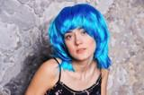 pretty girl in blue wig on grey background