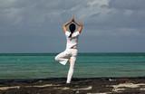 Eine Frau in der Yogastellung Baum am Strand des Preskil Beach Resort von Mauritius