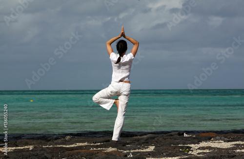 Eine Frau in der Yogastellung Baum am Strand des Preskil Beach Resort von Mauritius © Anke Thomass