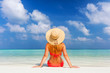 Beautiful young woman in sunhat sitting relaxed on tropical beach in Maldives