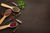 Assortment of tea in wooden spoons on dark background