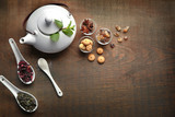 Teapot, sweets and spoons with tea on wooden table