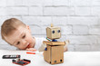 little boy plays with the robot at home. Child exploring robot