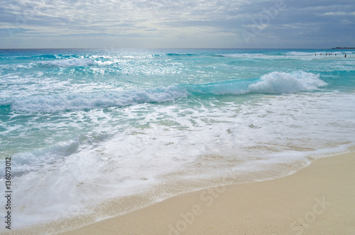 Turquoise waves at sandy beach
