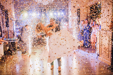 Bride and groom first dance at wedding reception with firewoks and confetti. Kissing and swing couple in love.