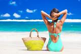 back view of a woman in bikini with beach bag