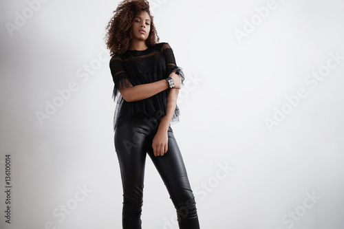 black woman wears leather pants and hugs herself Slika na platnu