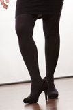 Female legs in black pantyhose heeled shoes
