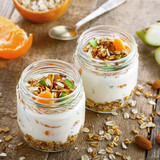 Granola with yogurt and fruits in a rustic jar. Delicious healthy American food for breakfast. Traditional US snack.